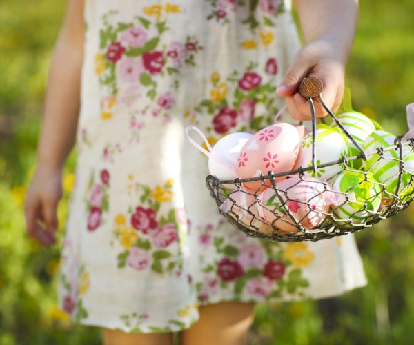 Close up of colorful Easter eggs in a basket in hands of a little girl