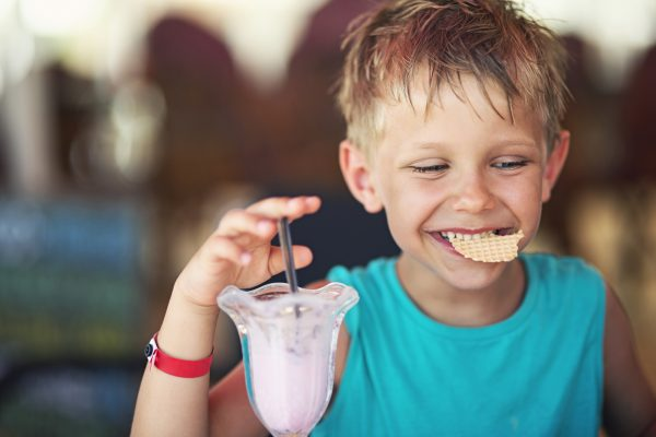 Little boy eating ice cream at restaurant