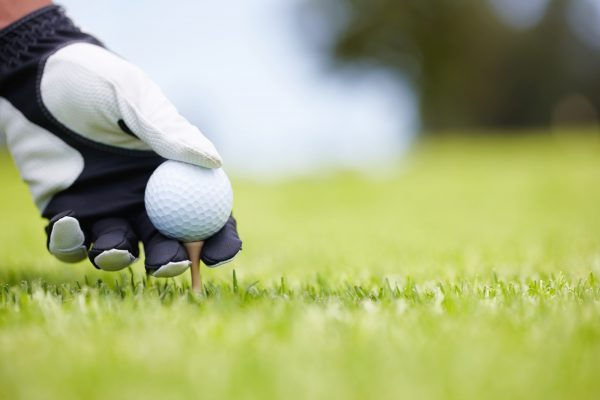 Golf ball being carefully balanced on a golf tee