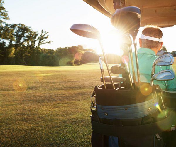 Shot of a retired couple driving a golf cart across a green