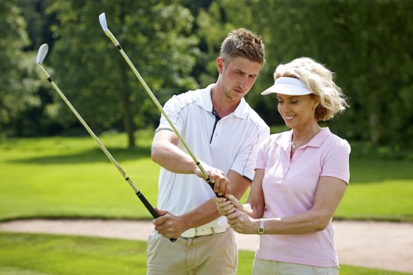 Male golf pro teaching female golfer the proper grip at golf course